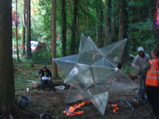 Folk working on an installation opposite one of the woods stages.